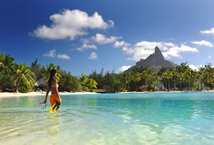 Woman getting into the innerlagoon with snorkeling material at the hotel Le Meridien Bora Bora facing the Otemanu mount