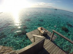 woman relaxing in a sunchair on her overwater bungalow deck in french polynesia