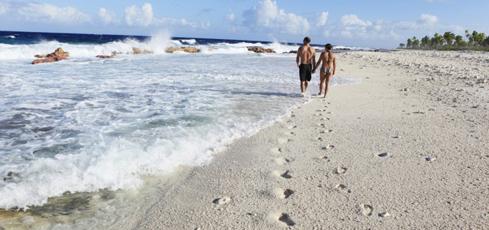 Couple walking on a beach of Mangareva island