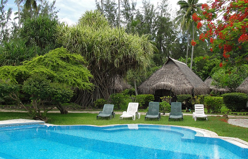 Swimming pool and bungalows at the hotel Hibiscus in Moorea island