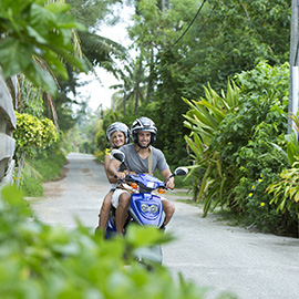 Couple riding a scooter in the paths of the Islands of Tahiti
